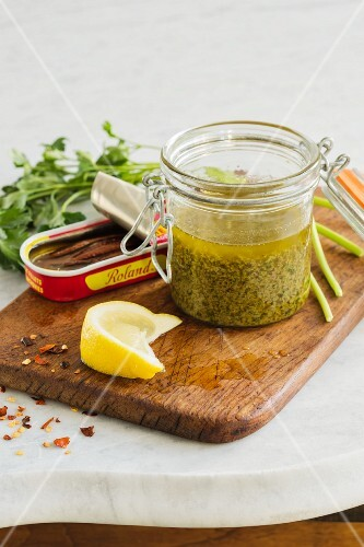 Anchovy sauce with lemons and capers in a flip-top jar
