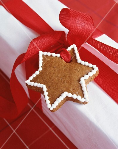 Gingerbread star attached to gift by red ribbon