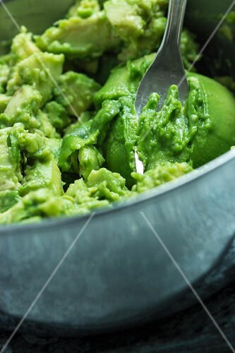 A avocado being mashed with a fork