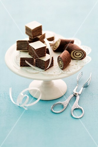 Chocolate and orange cubes and mini Swiss rolls on a cake stand
