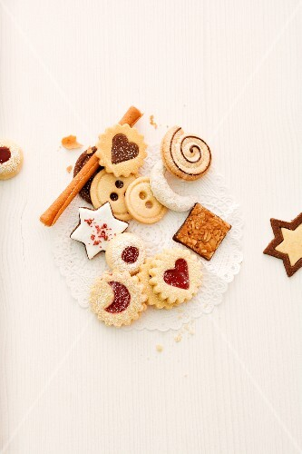 Various Christmas biscuits with cinnamon sticks (seen from above)