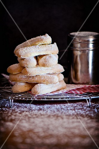 A stack of homemade sponge fingers on a cooling rack