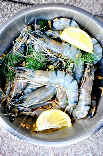 Fresh king prawns with lemon wedges and fennel leaves (seen from above)