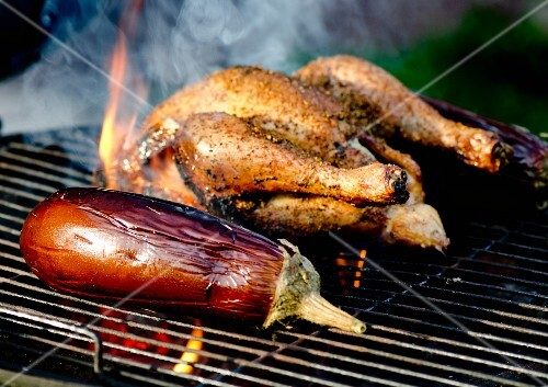 A whole chicken and an aubergine on a barbecue