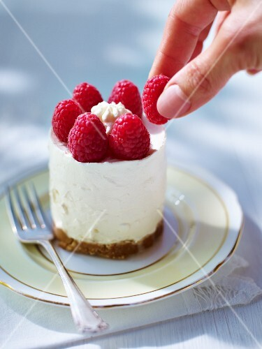 A cheesecake being garnished with raspberries