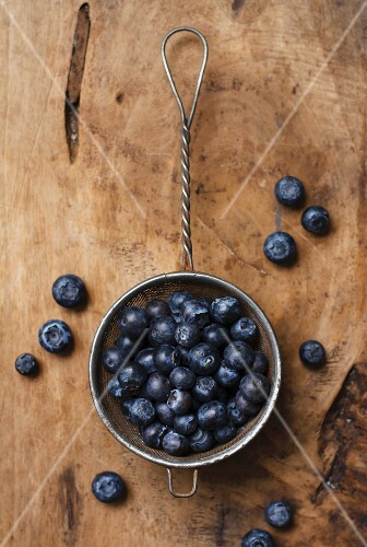 Blueberries in a sieve on a wooden surface