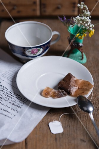 A used tea bag and rock sugar on a saucer next to a tea cup