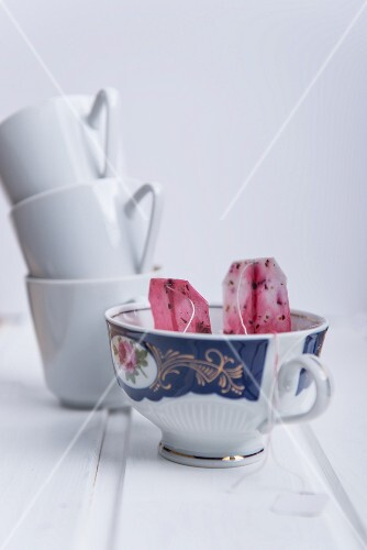 Used fruit tea bags in a porcelain cup with a stack of mugs in the background