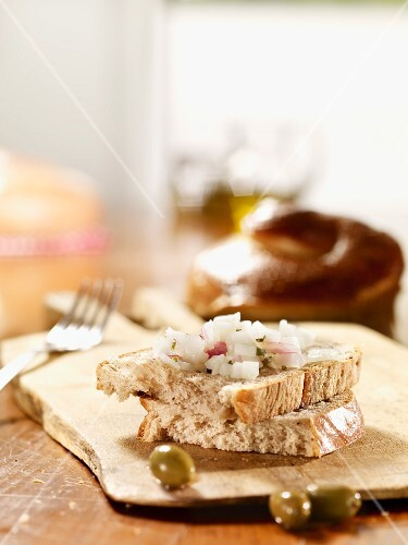 Two slices of olive bread with diced onion on a wooden board