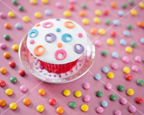 A cupcake decorated with colourful fondant icing