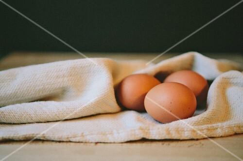 Three brown eggs on a tea towel