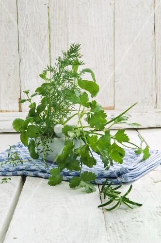 Various fresh herbs in a mortar