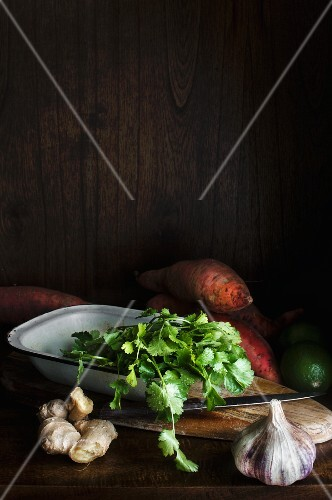 An arrangement of ingredients with sweet potatoes, ginger, coriander and garlic