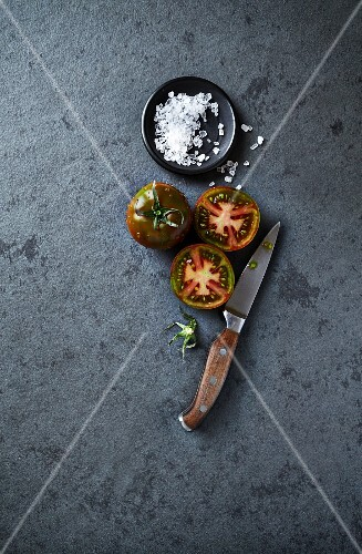 An arrangement of black tomatoes, coarse salt and a kitchen knife (seen from above)