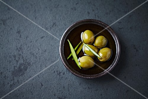 Green olives in oil with rosemary (seen from above)