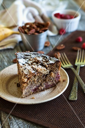 A slice of banana cake with raspberries and pecan nuts