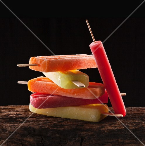 A stack of various fruit ice lollies on a wooden surface