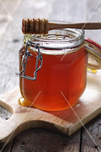 Honey in a jar dripping from a honey spoon