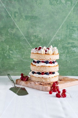 A sponge cake tower with fresh berries and butter cream