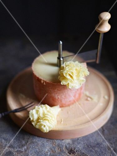 Tete de Moine cheese on a board with a cutter and two rosettes