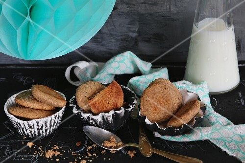 Almond flour and honey cakes in homemade clay dishes with a turquoise lantern and a bottle of milk partially visible in the background