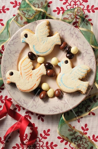 Bird biscuits on a plate with chocolate-coated nuts