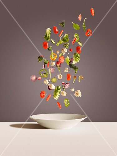 Slices of vegetables falling onto a white plate