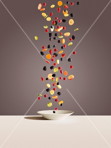 Fresh berries and sliced fruit falling onto a white plate