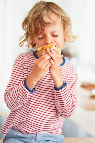 A little boy a taking a bite out of a muffin