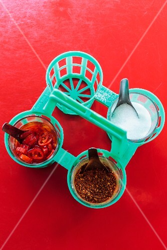Sugar, chilli flakes and chillis in vinegar on a red table on a noodle shop (Thailand)
