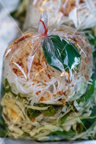 Rice noodles with lettuce in a plastic bag to take away (Thailand)