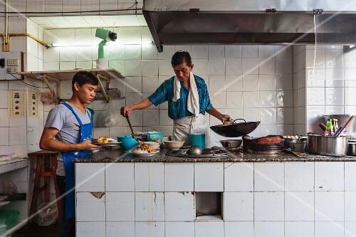 Cooks in a restaurant kitchen (Bangkok, Thailand)