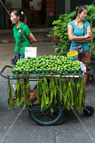 Oriental women with a mobile sales stand selling limes and petai beans (Thailand)