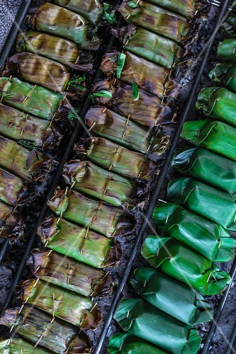 Stuffed banana leaf parcels on a barbecue (Thailand)