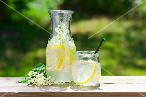 Lemonade with elderflowers on a table outside