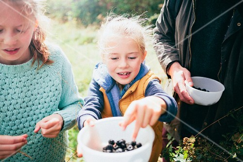 Two girls holding blackberries in a bowl