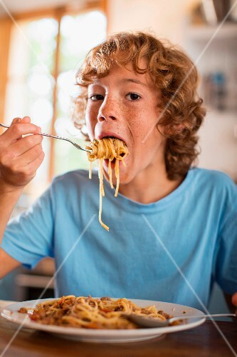 A teenage boy eating spaghetti at a dining table