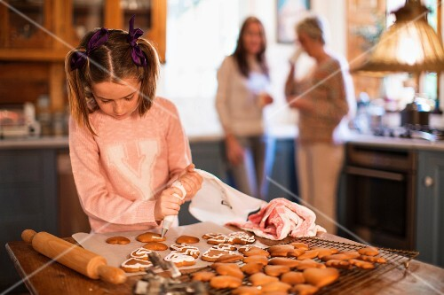 A girl icing homemade cinnamon and honey biscuits