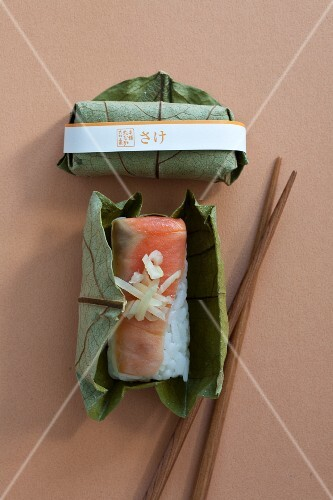 Salmon sushi with ginger strips wrapped in a leaf