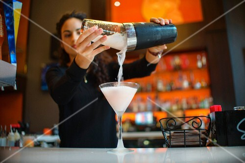 A young woman pouring a finished cocktail into a glass