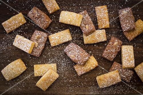 Financiers dusted with icing sugar on a wooden surface