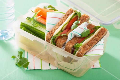 A cheese sandwich and raw vegetables in a lunch box
