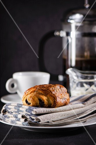 A chocolate croissant and a cup of coffee