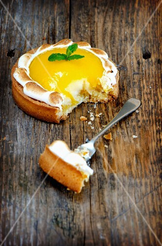 A lemon meringue tartlet on a wooden surface with a bite taken out of it