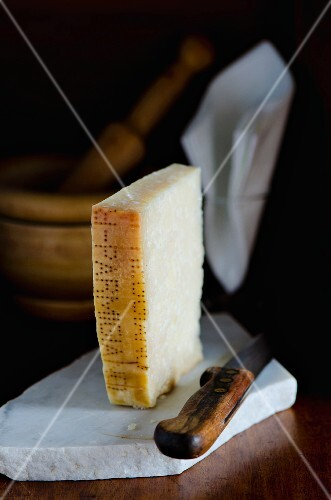 A slice of Parmesan cheese with a knife on a slab of marble