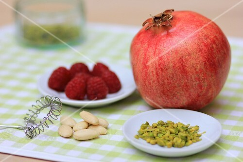 A pomegranate, nuts and raspberries