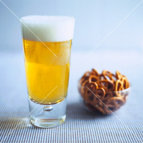 A glass of lager and a bowl of pretzels