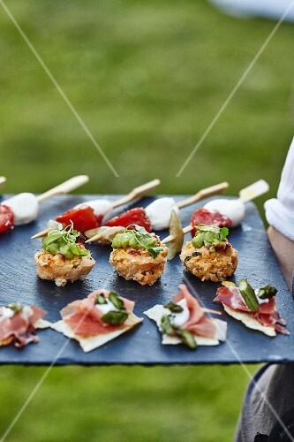 Various canapés on a slate platter