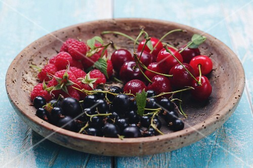 Various summer fruits in a wooden bowl