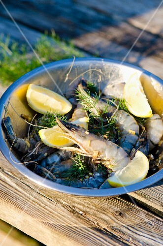 Marinated king prawns with lemons and herbs in a stainless steel bowl